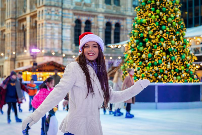 Happy woman has fun on a Christmas ice rink royalty free stock photos