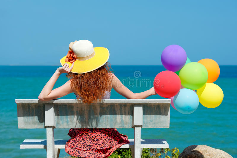 Happy woman in hat with balloons stock images