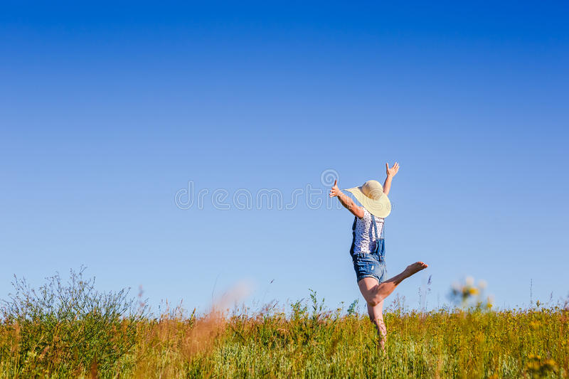 Happy woman in hat jumping in green field against blue sky. Summer vacation concept stock image