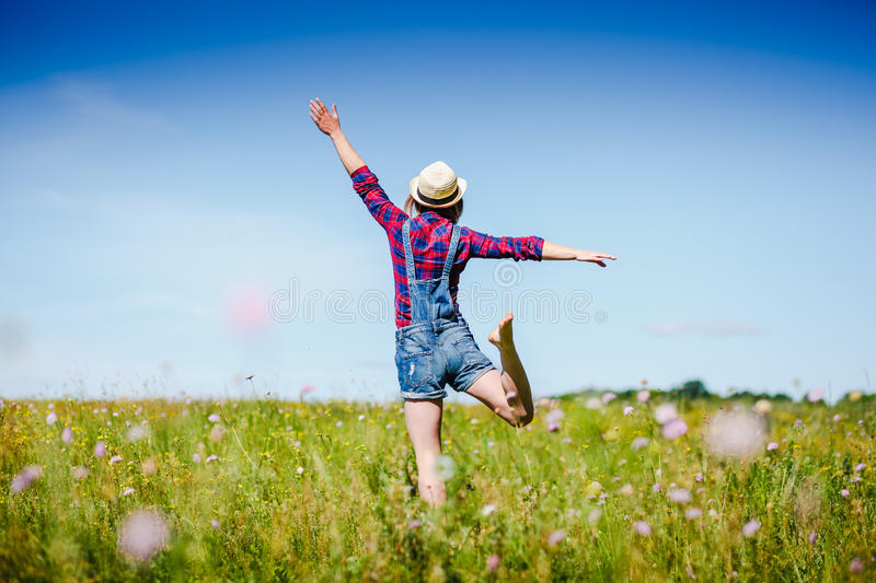 Happy woman in hat jumping in green field against blue sky. Summer vacation concept royalty free stock photography