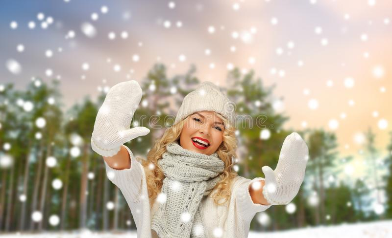 Happy woman in hat and scarf over winter forest stock photos