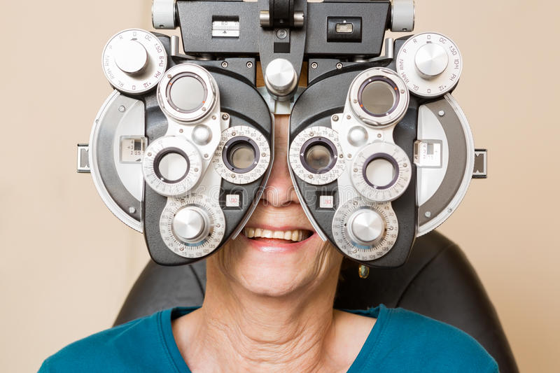 Happy Woman Having An Eye Test. Happy senior woman looking through phoropter during eye exam royalty free stock image