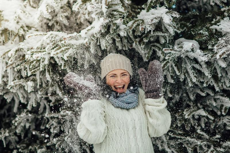 Happy woman having fun with snow falling from trees royalty free stock image