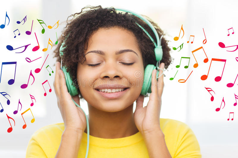 Happy woman with headphones listening to music. People, technology and leisure concept - happy african american young woman sitting on sofa with headphones stock photos