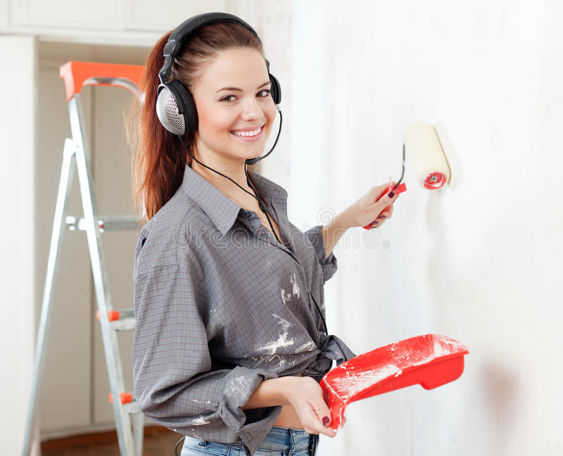 Happy woman in headphones paints wal stock photo