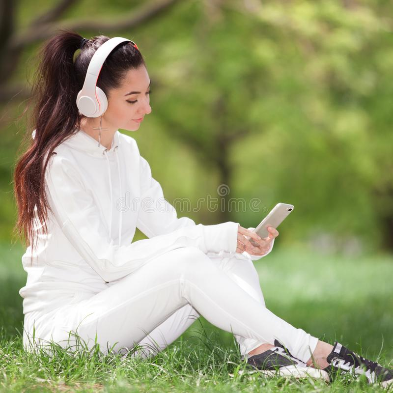 Happy woman with headphones relaxing in the park. Beauty nature scene with colorful background. Fashion woman enjoying the music stock images