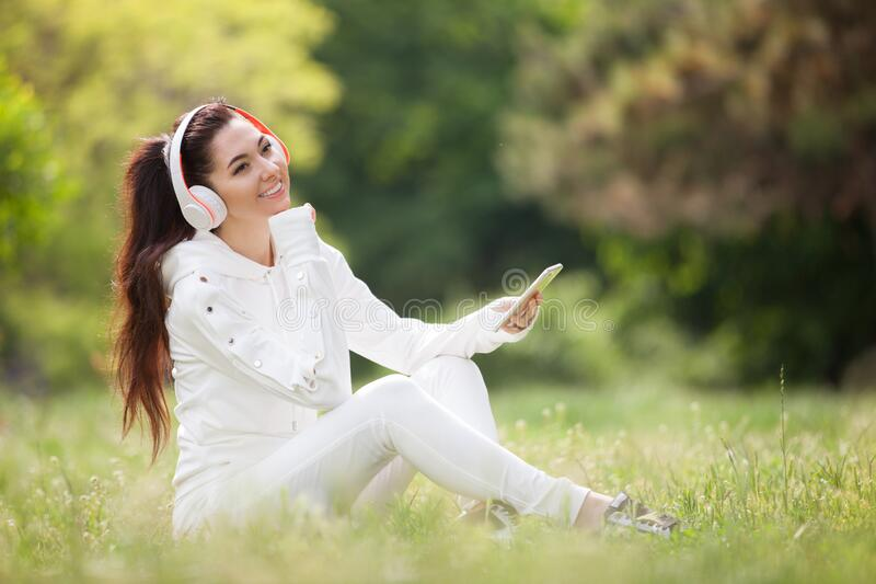 Happy woman with headphones relaxing in the spring park. Beauty nature scene with colorful background. Fashion woman enjoying the stock photo