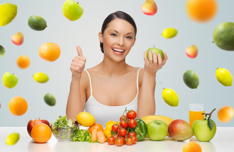 Happy woman with healthy food showing thumbs up. People, diet, gesture and vegetarian concept- happy asian woman with healthy food showing thumbs up over gray royalty free stock images