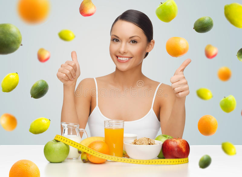 Happy woman with healthy food showing thumbs up. People, gesture and diet concept- happy asian woman with healthy food showing thumbs up over gray background stock images