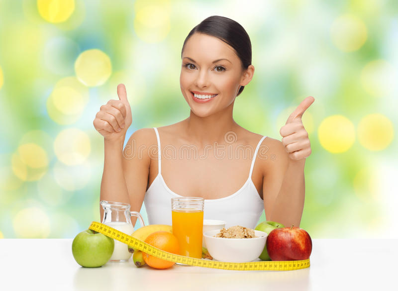 Happy woman with healthy food showing thumbs up. People, gesture and diet concept- happy asian woman with healthy food showing thumbs up over green lights royalty free stock images