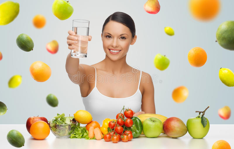 Happy woman with healthy food showing water glass. People, diet and vegetarian concept - happy asian woman with healthy food showing glass of water over gray stock photos