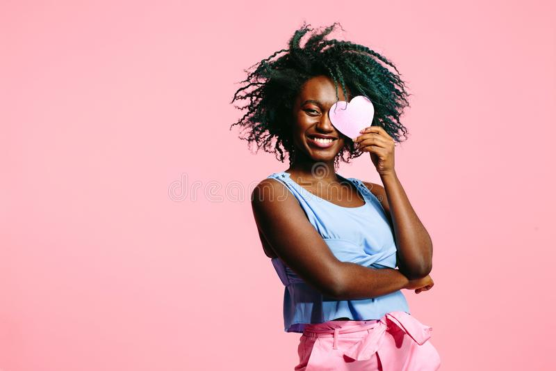 Woman smiling and holding a pink heart covering her eye, be my Valentine stock photos