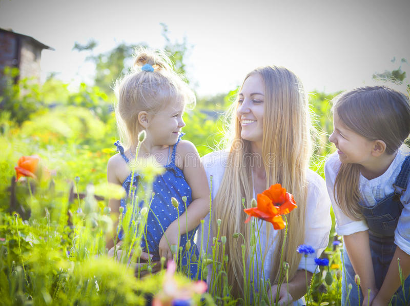 Happy woman and her daughters in the blooming spring garden stock photo