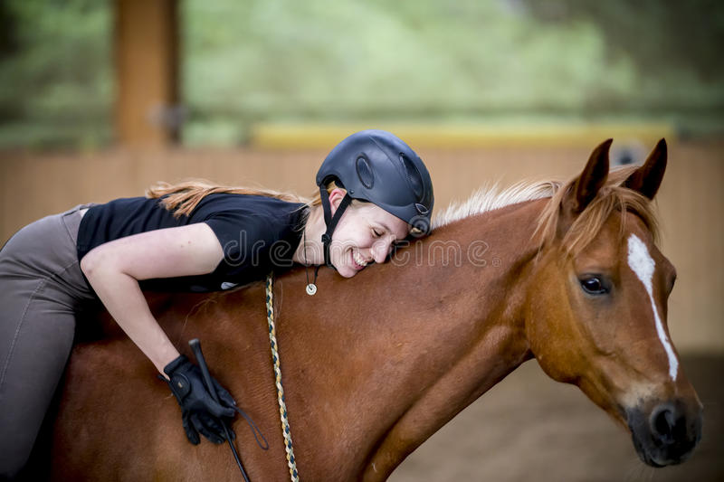 Happy woman on her horse. Young happy woman on her horse, enfolding her horse stock images