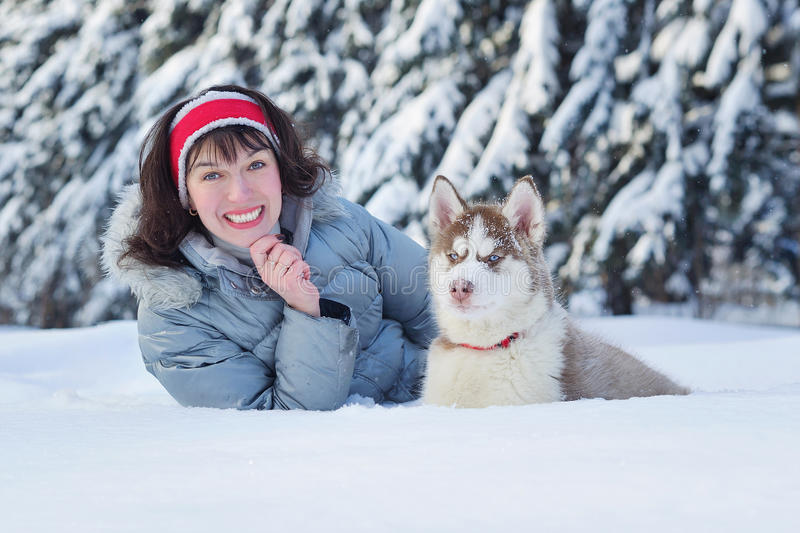 Happy woman and her Husky puppy. Cheerful woman having fun with her little cute Siberian Husky puppy in winter forest full of snow. Lifestyle concept royalty free stock images