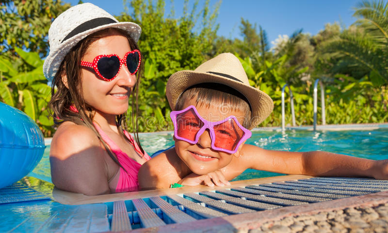 Happy woman and her son wearing sunglasses in pool. Happy women and her son wearing sunglasses and hats in the swimming pool outside in summer stock image