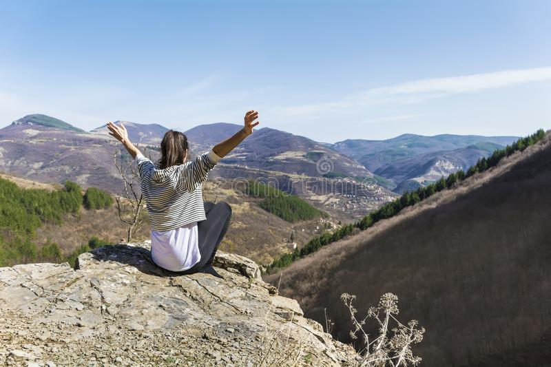 Happy Woman in a High Mountain. Happy woman relaxing in a high mountain royalty free stock image