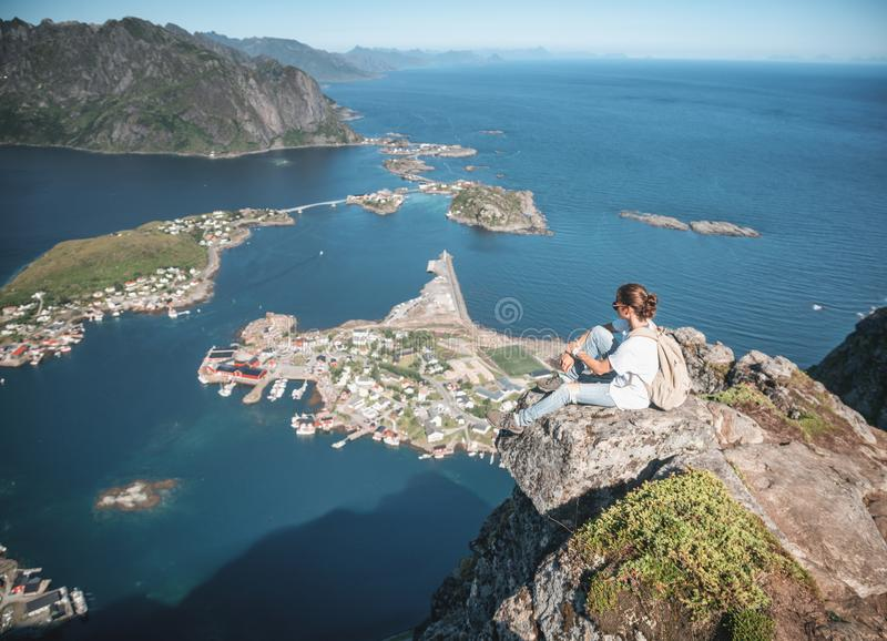 Happy woman hiker enjoying scenic view at the top of Reinebringen hike above Reine village in the Lofoten archipelago, travel to royalty free stock photo