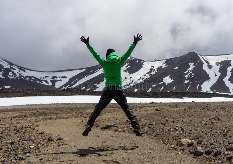 Happy woman hiker jumping in Tongariro national park. In New Zealand stock image