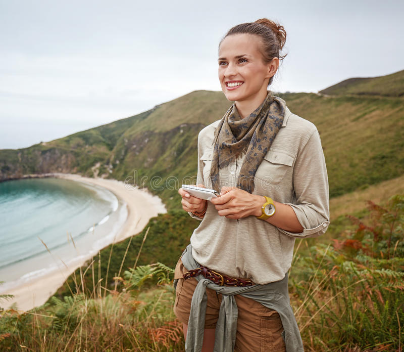 Happy woman hiker writing sms in front of ocean view landscape. Into the wild in Spain. happy adventure woman hiker writing sms in front of ocean view landscape royalty free stock photography