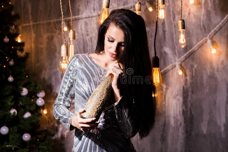 Happy woman hold bottle of champagne over christmas interior background. New Year, holiday, celebration, winter concepts royalty free stock photography