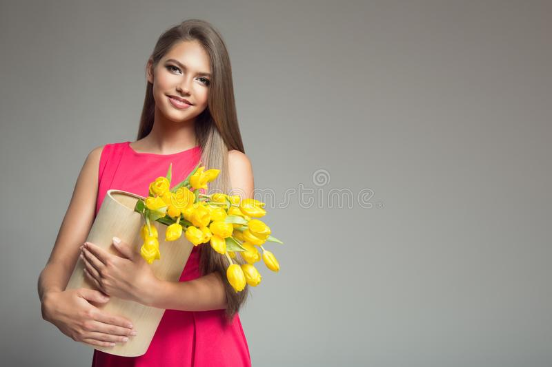 Young happy woman holding basket with yellow tulips. Gray background. stock photos