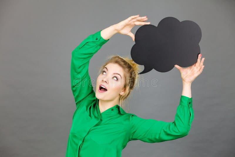 Happy woman holding black thinking bubble royalty free stock image