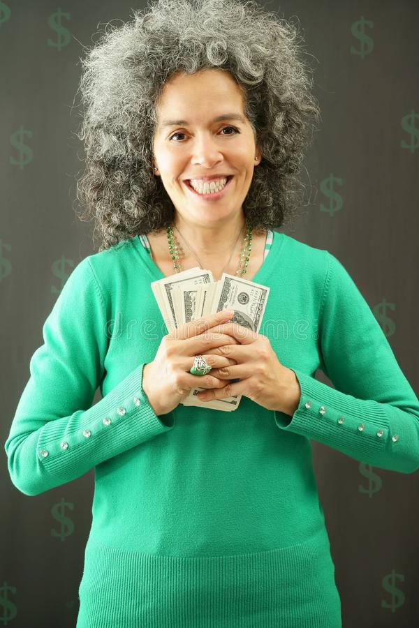 Happy woman holding bundles of US$ dollar notes on dark background. A smiling woman with greying hair is holding bundles of 100 US dollars. She is wearing a stock image