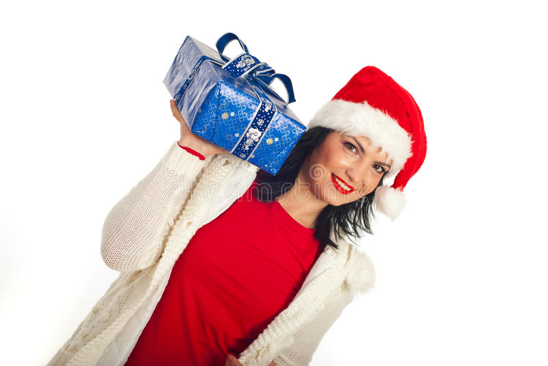 Happy woman holding Christmas gift. Happy woman in Santa hat holding up a blue Christmas gift isolated on white background stock photos