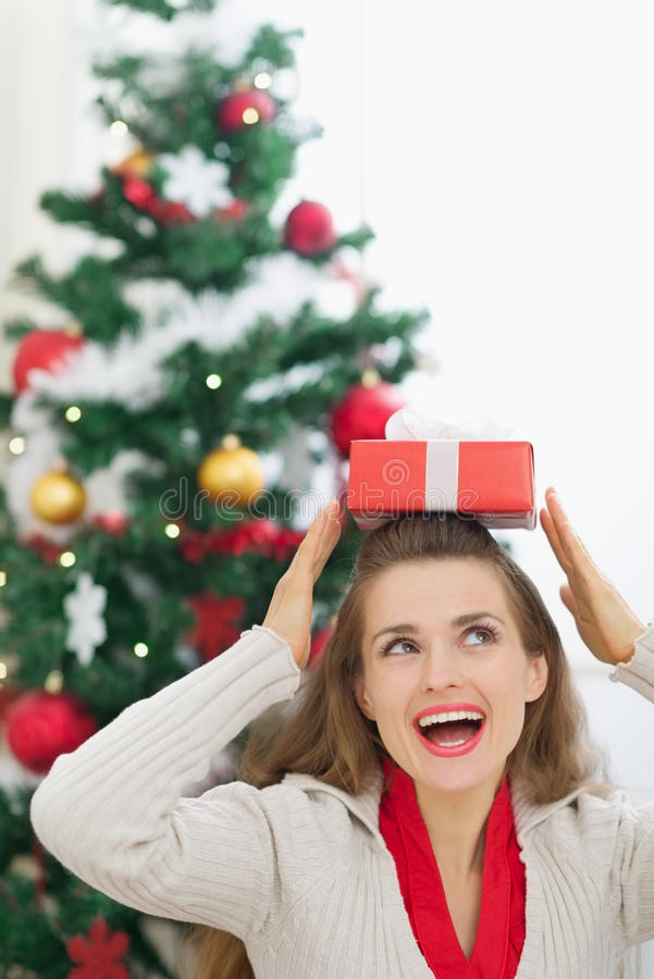 Download Happy Woman Holding Christmas Present Box On Head Stock Photo - Image: 26238624