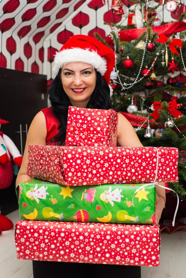 Happy woman with Christmas gifts. Happy woman holding Christmas presents in front of Xmas tree stock photos