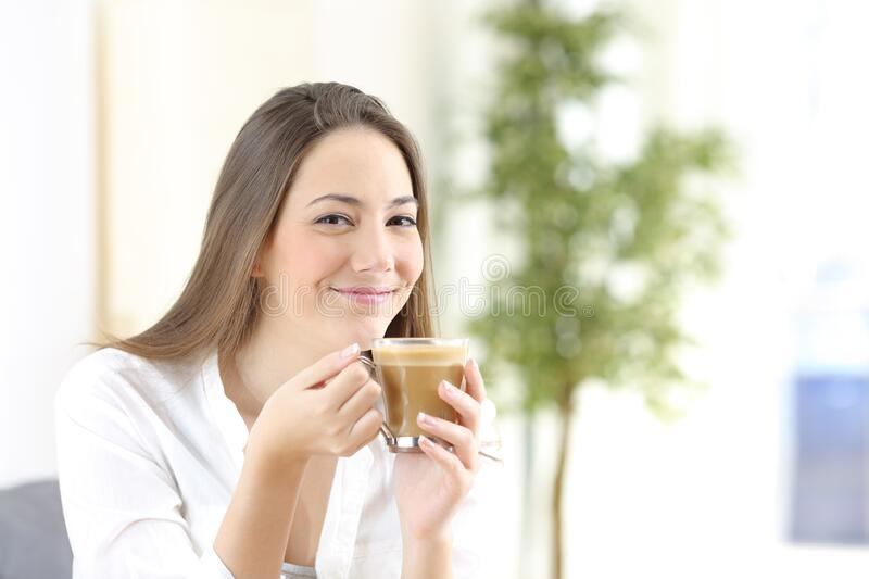 Happy woman holding a coffee cup looking camera. Sitting at home royalty free stock photography