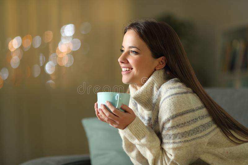 Happy woman holding coffee cup in winter at home stock photo
