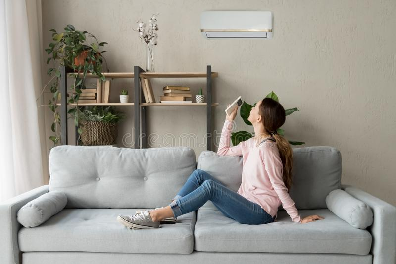 Happy woman holding cooler system remote controller enjoy fresh air. Happy woman rests on couch in modern cozy living room looks up on wall holds cooler system stock image