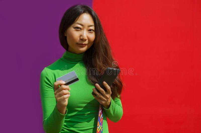 Happy woman holding credit card and smartphone on colourful background. Happy asian woman holding credit card and smartphone on colourful background stock photography