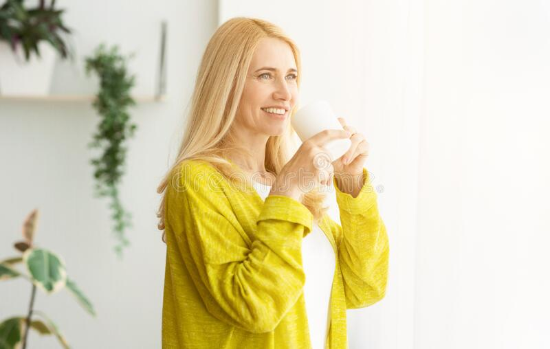 Happy woman holding cup of tea and looking at window stock images