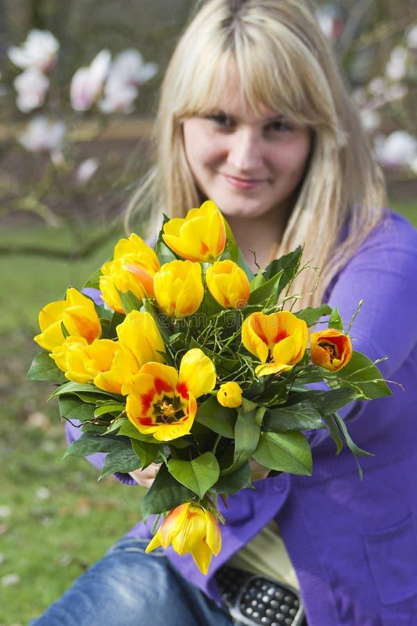 Happy woman holding flowers stock photos