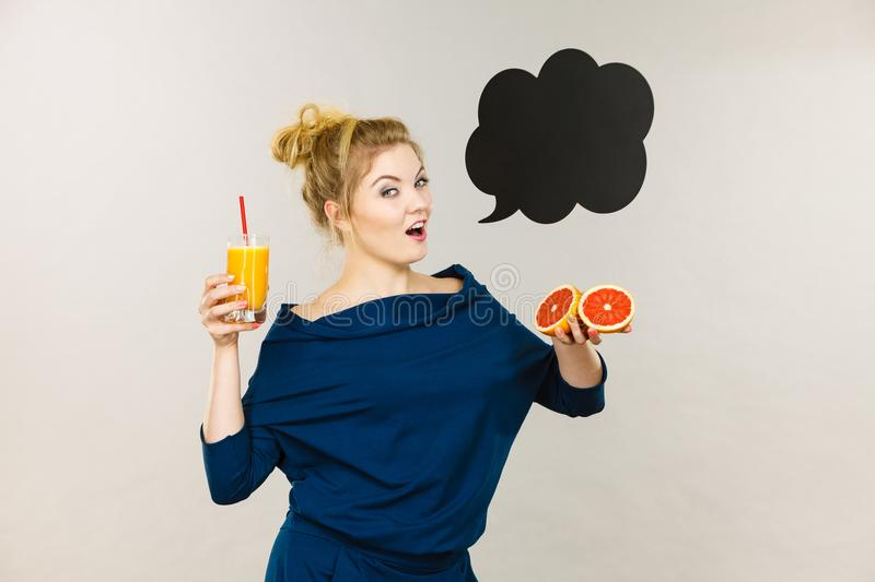 Happy woman holding fresh orange juice. Happy woman holding fresh orange grapefruit juice. Healthy fruit drink smoothies concept, black thinking or speech bubble royalty free stock photo