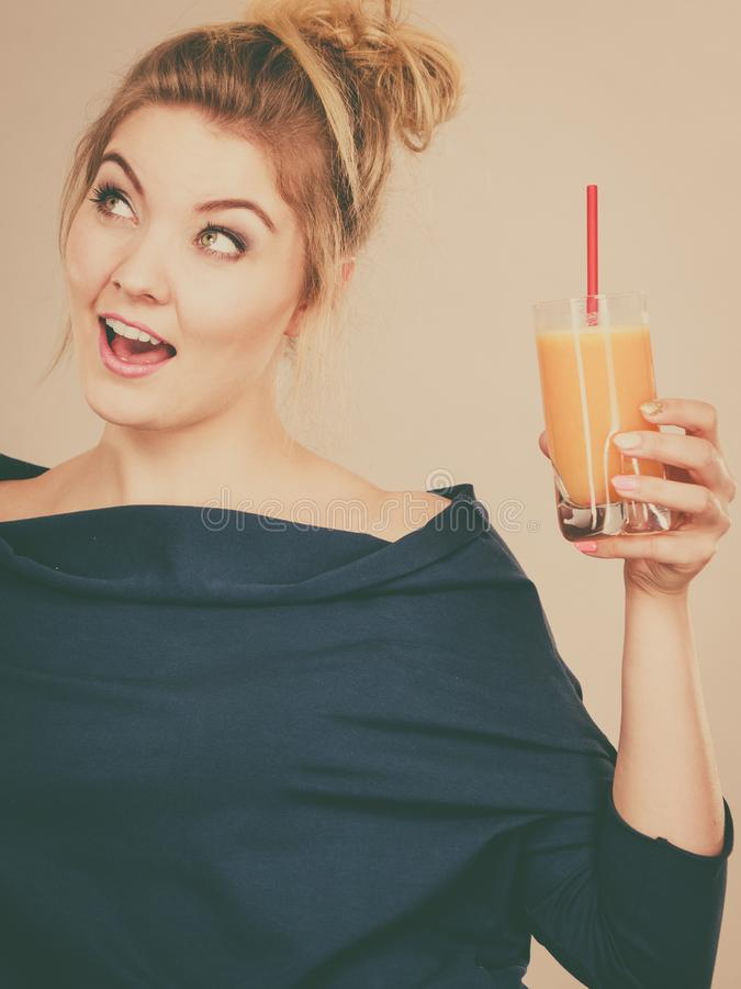 Happy woman holding fresh orange juice royalty free stock photo