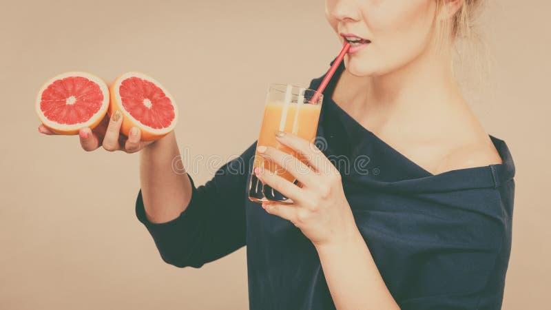 Happy woman holding fresh orange juice. Happy woman holding fresh orange grapefruit juice. Healthy fruit drink smoothies concept royalty free stock image