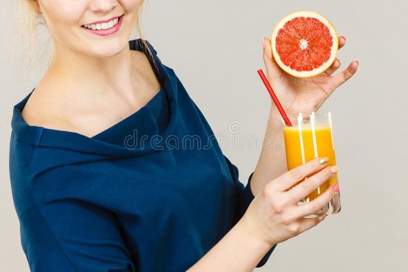 Happy woman holding fresh orange juice. Happy woman holding fresh orange grapefruit juice. Healthy fruit drink smoothies concept stock images