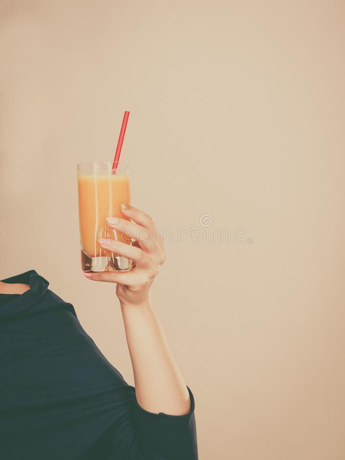 Happy woman holding fresh orange juice. Happy woman holding fresh orange grapefruit juice. Healthy fruit drink smoothies concept royalty free stock photography