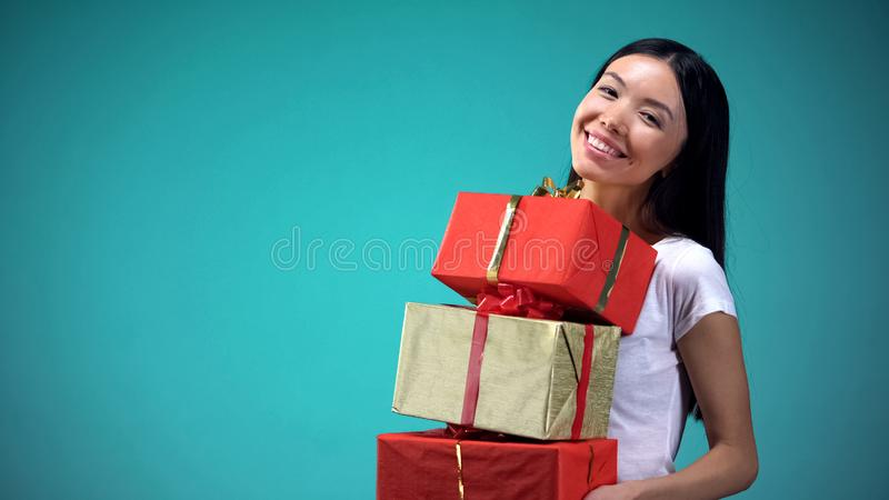 Happy woman holding gift boxes, internet store of original presents for everyone royalty free stock images