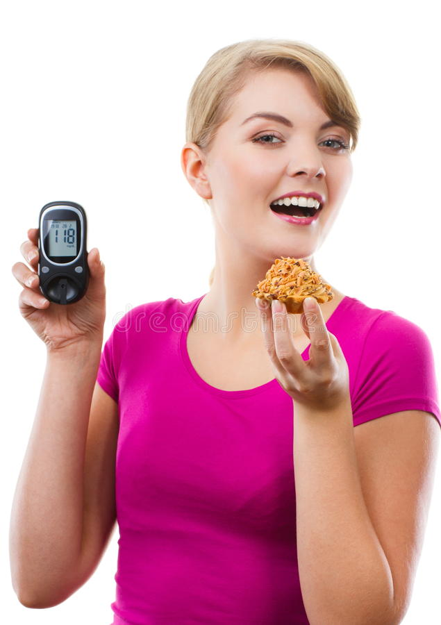 Happy woman holding glucometer and eating fresh cupcake, measuring sugar level, concept of diabetes. Happy woman holding glucose meter with positive result of stock photo
