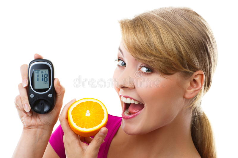Happy woman holding glucometer and eating fresh orange, measuring and checking sugar level, concept of diabetes royalty free stock images