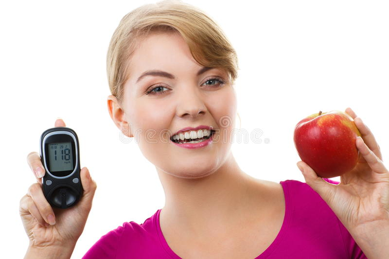 Happy woman holding glucometer and fresh apple, measuring and checking sugar level, concept of diabetes royalty free stock images