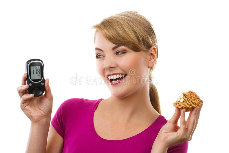 Happy woman holding glucometer and fresh cupcake, measuring and checking sugar level, concept of diabetes royalty free stock image