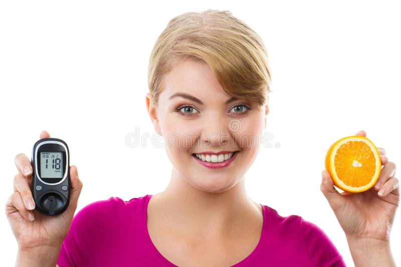 Happy woman holding glucometer and fresh orange, measuring and checking sugar level, concept of diabetes royalty free stock photos