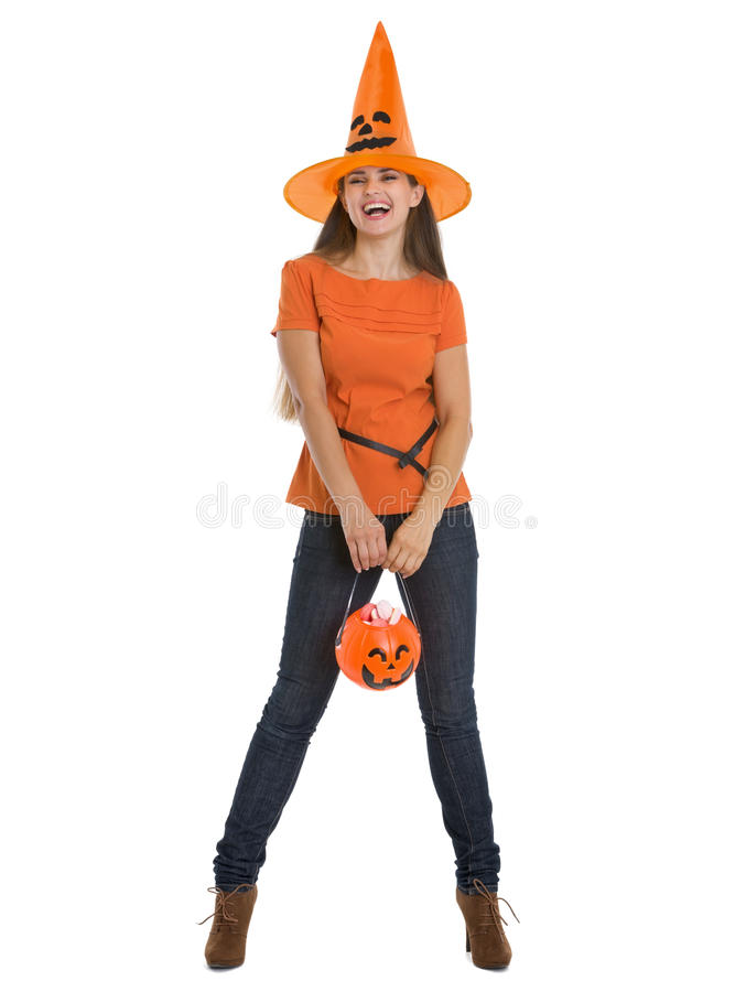 Happy woman holding Halloween bucket with sweets. Isolated on white royalty free stock photo
