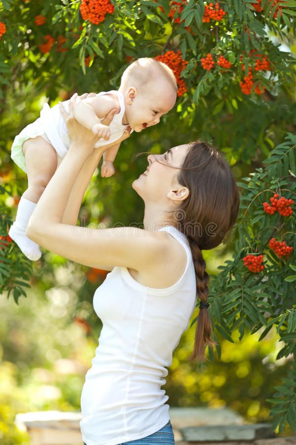 Free Happy Woman Holding In Arm A Baby In A Garden Stock Photography - 79097452